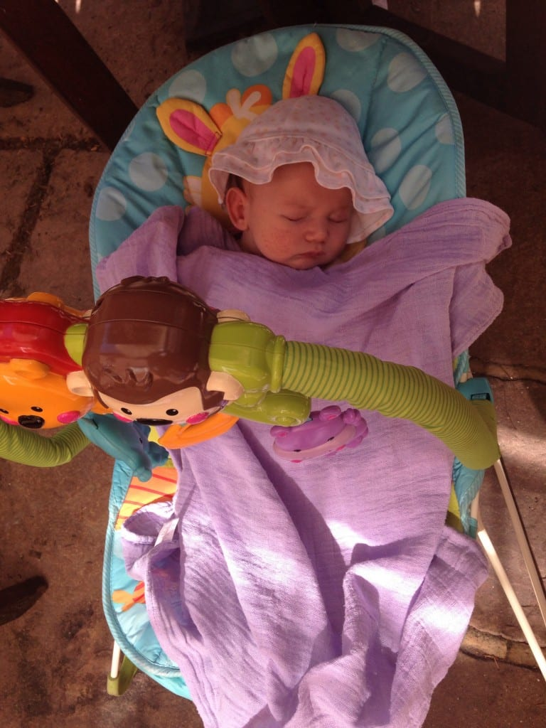 My Experience of A Cow's Milk Protein Allergy (CMPA) Baby - picture of tiny baby in a floppy hat asleep in a baby bouncer