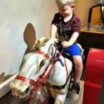 Logan riding hobby horse