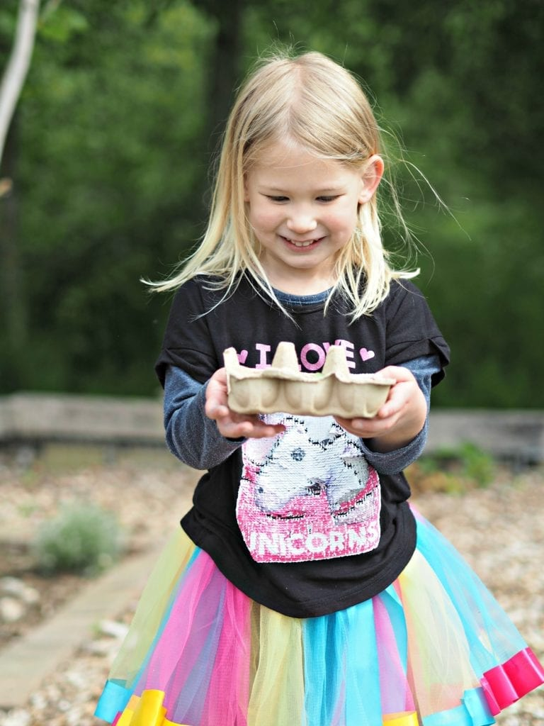 Aria at her muddy boots party holding an egg box full of colourful plants