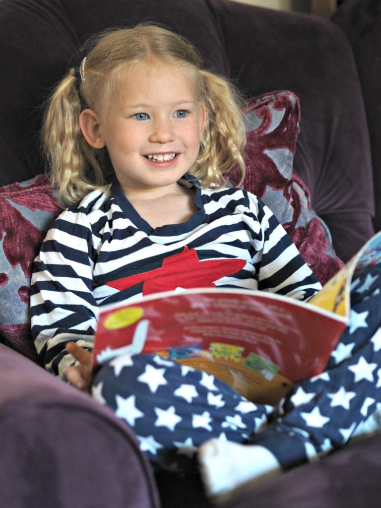 Is Tech Replacing Story Time for Families? Help the Book Trust on the 7th June. Aria sitting in an armchair, in her pjs, reading a book