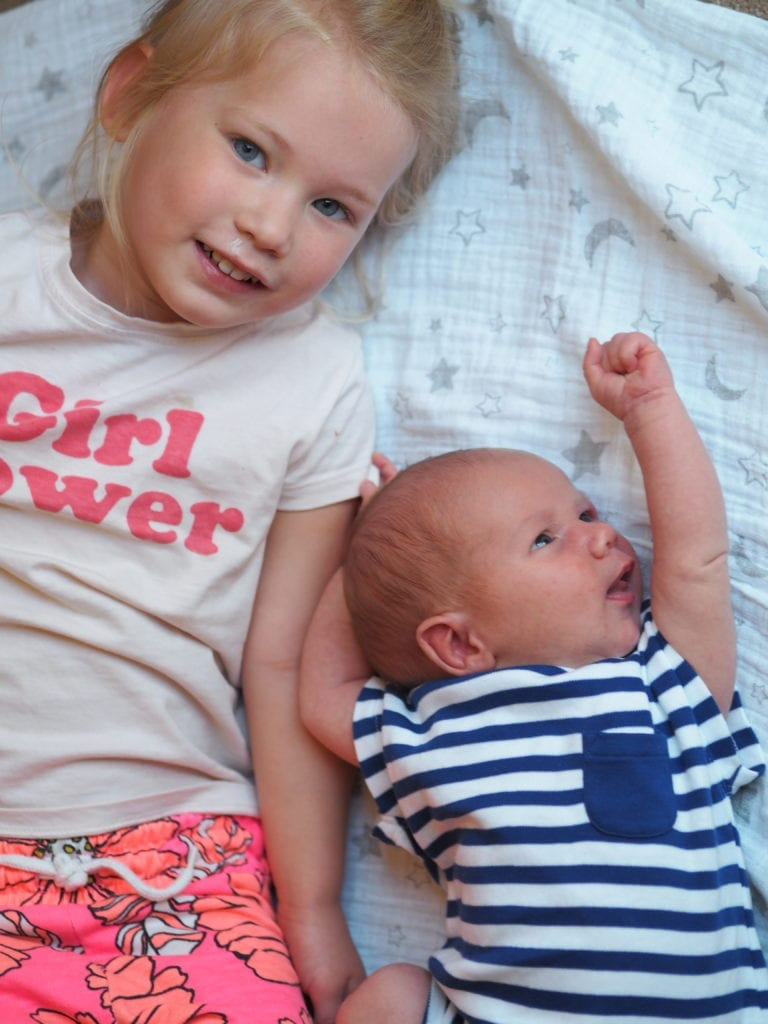 Aria and Bo laying on a may together with Bo as a newborn