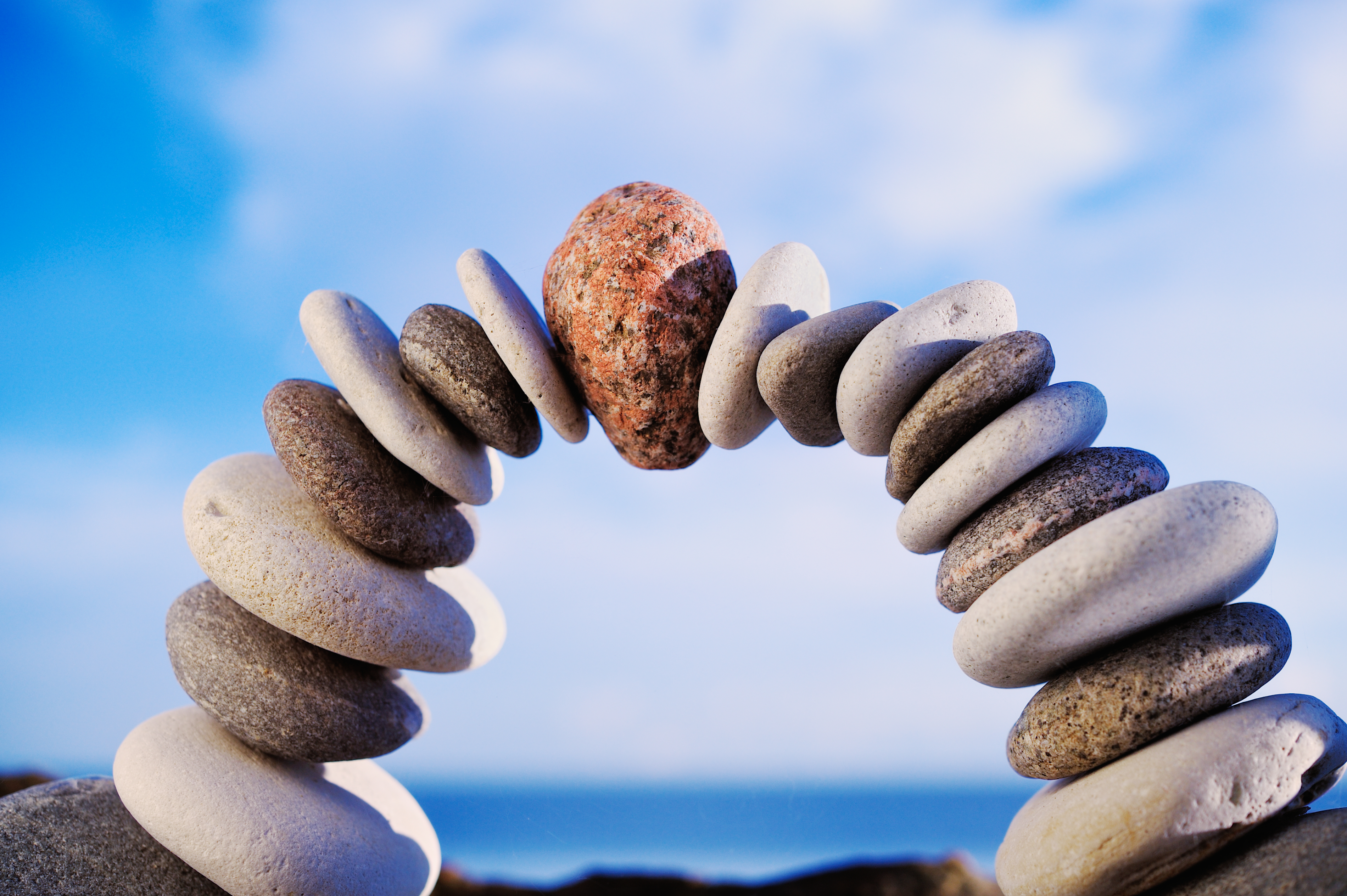 Meditation - rocks stacked in an arch and blue sky