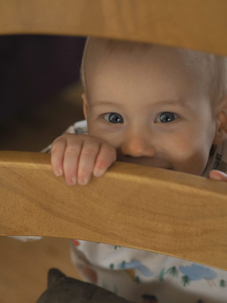 Making our Home more Baby Friendly - Bodhi peeking through wooden bars
