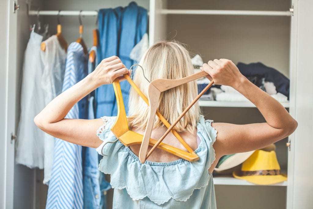 How to Revamp Old Clothes - girl near a wardrobe with clothes can not choose what to wear. Heavy Choice Concept has nothing to wear