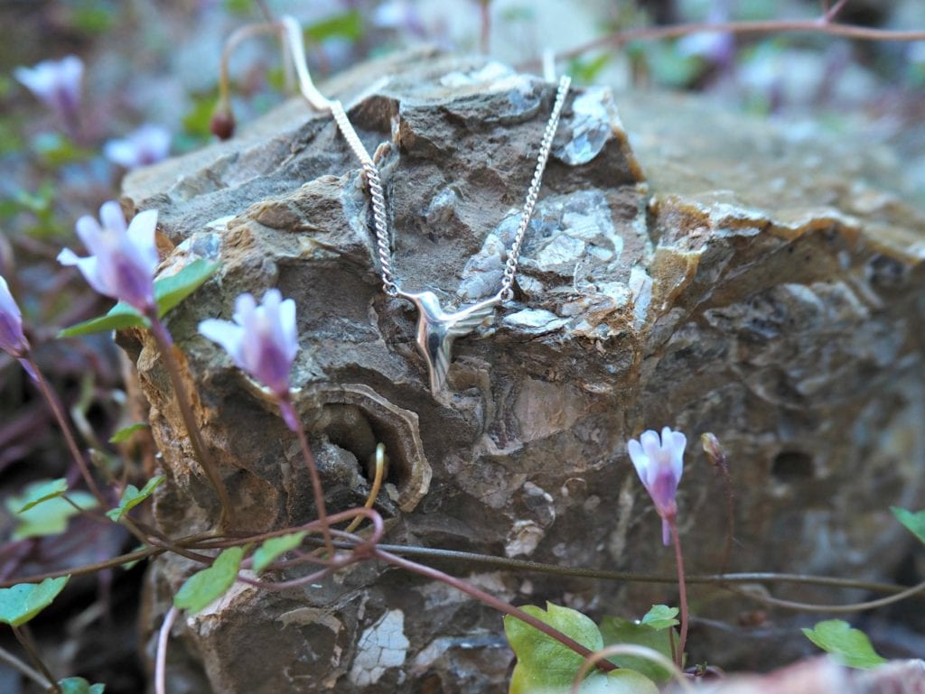 Jana Reinhardt Jewellery Review - necklace on a rock surrounded with small purple flowers