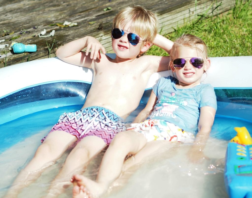 Our Summer Holiday Bucket List 2019 - Logan and Aria in the paddling pool relaxing with sunglasses on