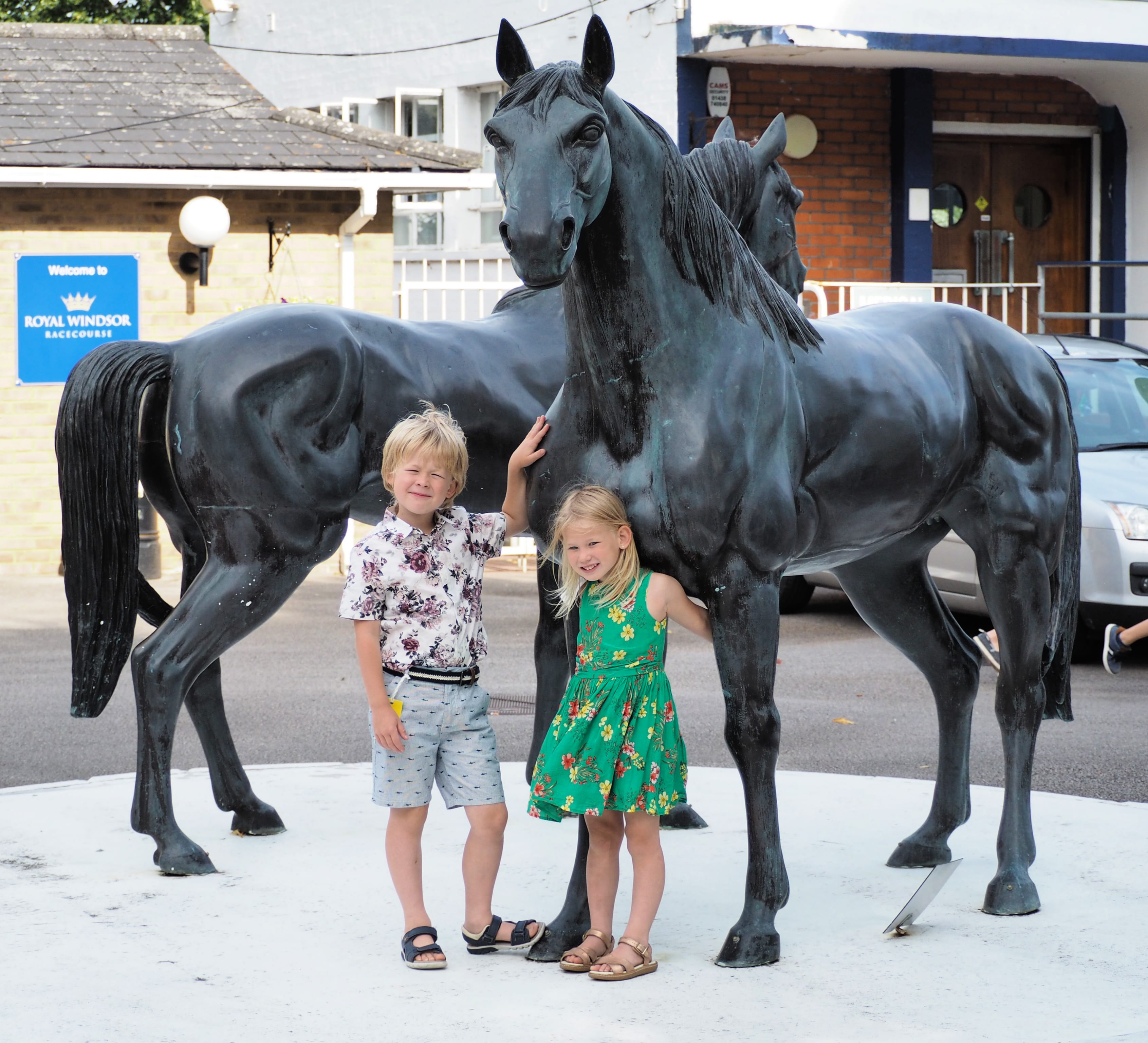 Logan and Aria standing by a statue of horses out the front of windsor races