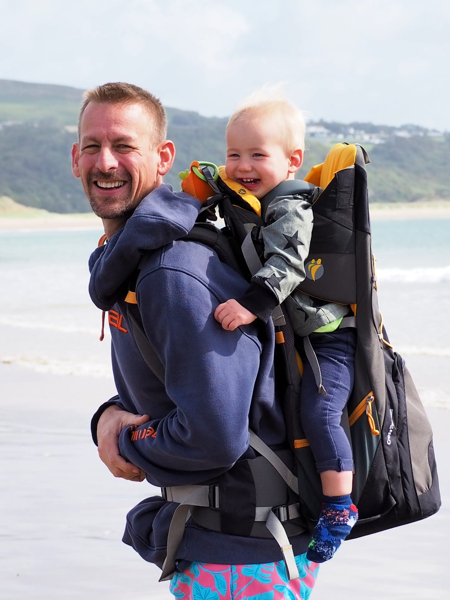 Ben with Bo in the carrier on the beach