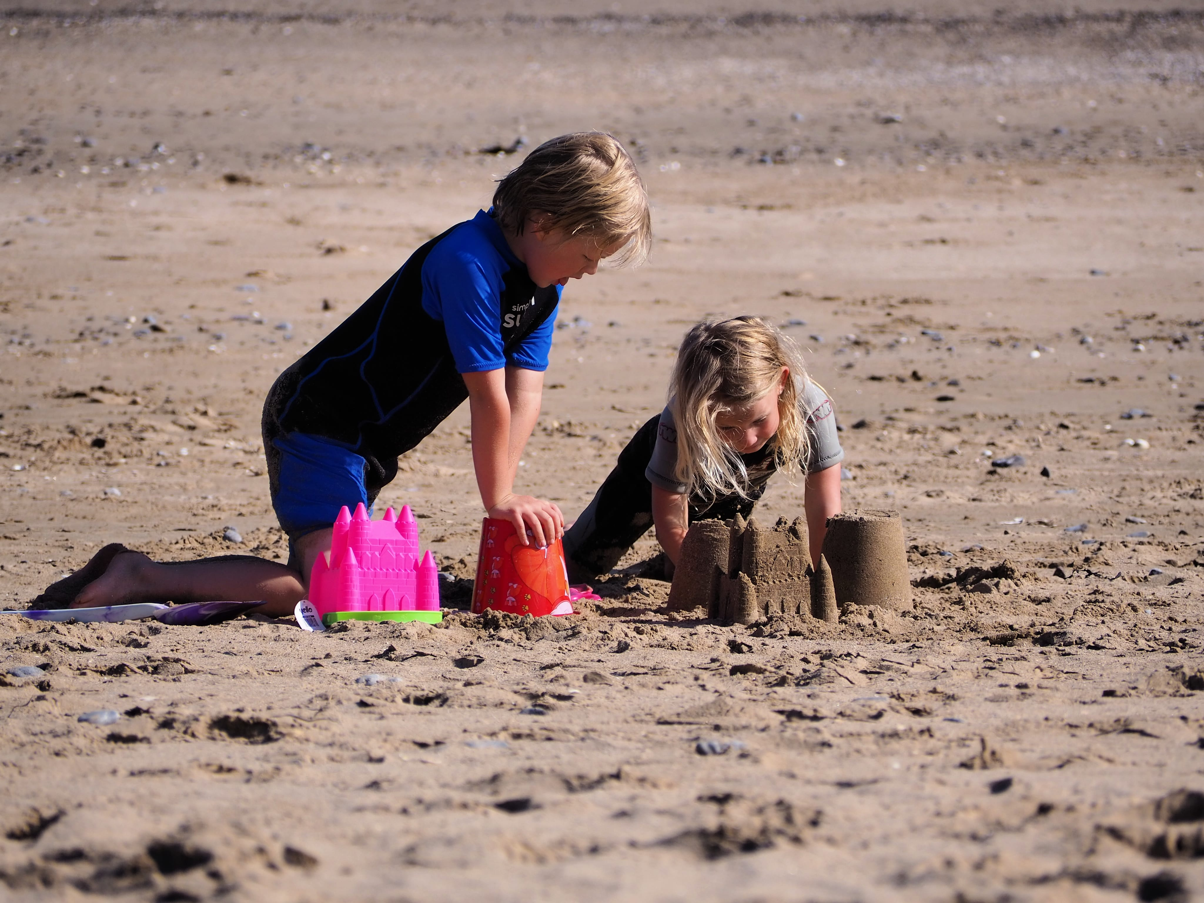 Logan and Aria building sandcastles