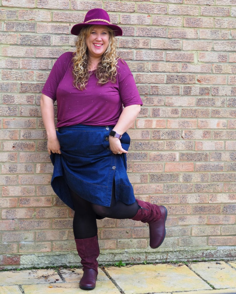 Me wearing a hat, maroon top and denim skirt in a pair of maroon hotter boots kicking one leg up to the side