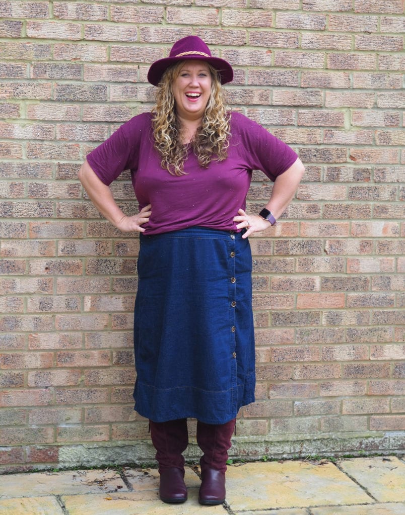 A picture of me laughing wearing a maroon top, denim skirt and maroon hotter boots