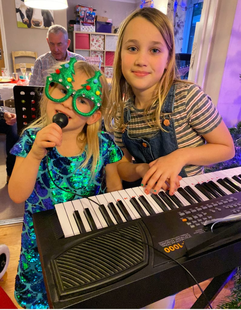 Aria with her concert singing and playing the keyboard in Christmassy clothes