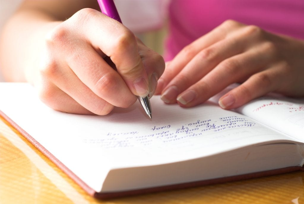 How to start a gratitude diary, picture of a diary and hands with a person in a pink top holding a pen and writing in it