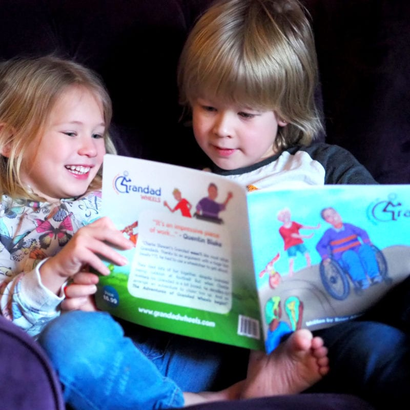 Logan and Aria sat on in an arm chair reading Grandad Wheels