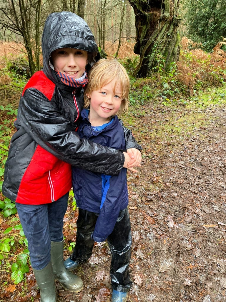 Logan and his cousin very wet in their waterproofs in the woods