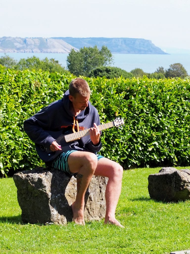 5 Reasons Why a Guitarist Needs a Snap Dragon in their Life - Ben sitting on a rock playing the guitar with grass behind him and the sea in the distance