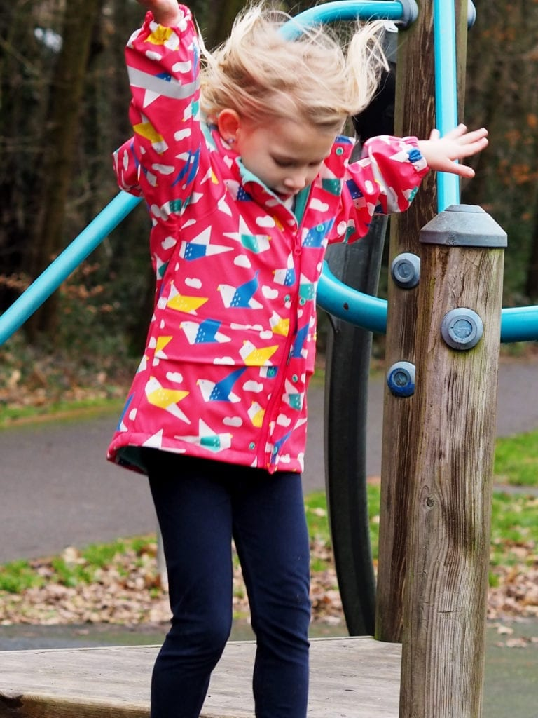 Aria jumping in pink Frugi coat and navy leggings - arms and hair in the air