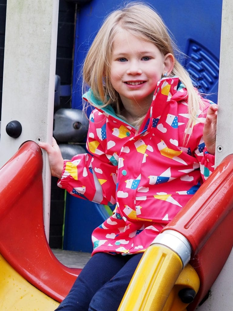 Aria sitting at the top of the slide in pink frugi coat