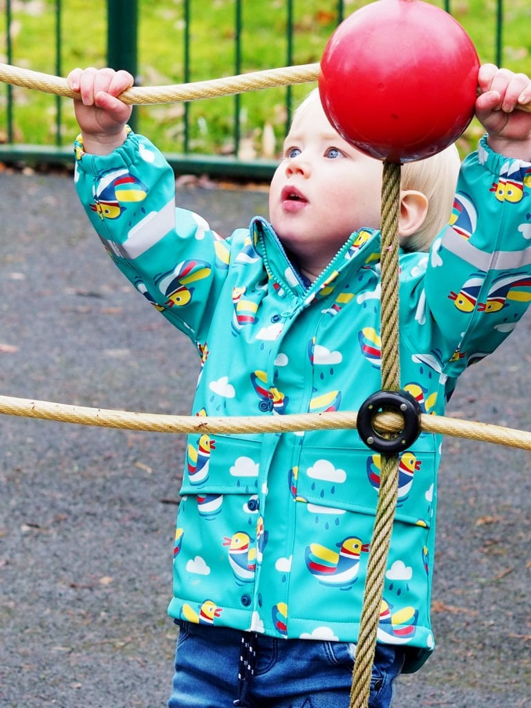 Bo climbing up ropes in Frugi coat with look of concentration on his face