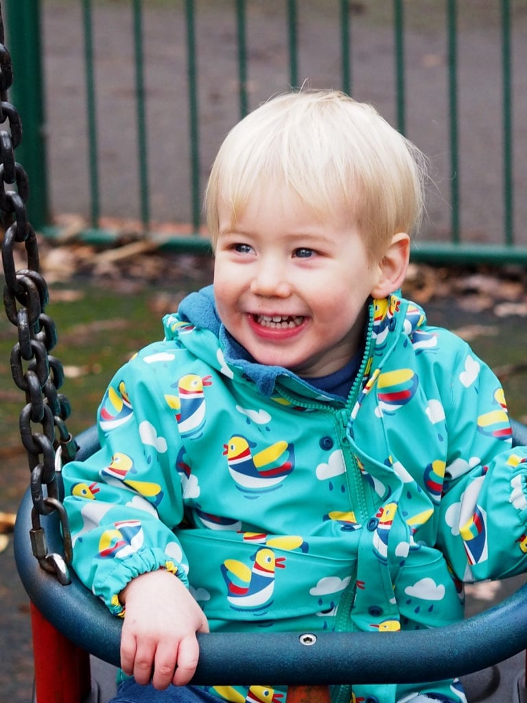 Bo sitting in swings with Frugi green coat with ducks on it