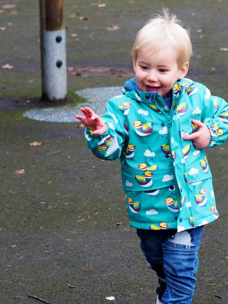 Bo running with arms in front of him wearing Frugi ducks puddle coat