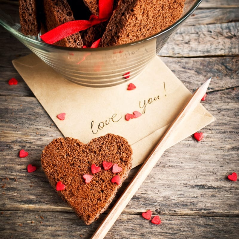 Eight Meaningful Things to do on Valentine's Day. Card with Message Love You in the Letter and Chocolate Cookies in the Shape of Heart at Valentine Day