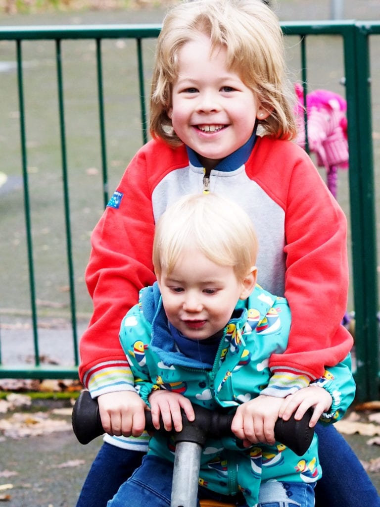 Logan and Bo sat on the bouncer wearing their Frugi jackets