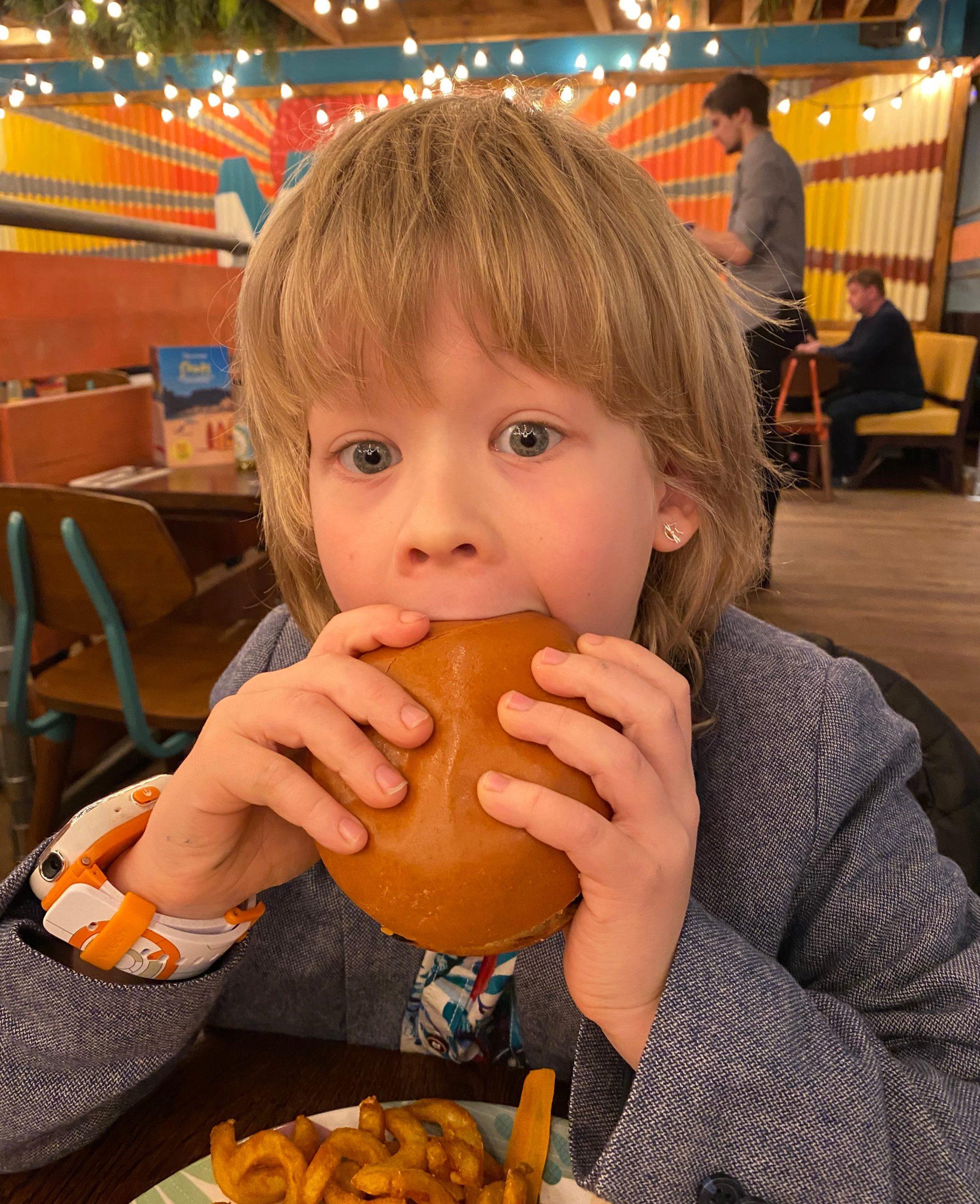 Logan eating a burger at Las Iguanas