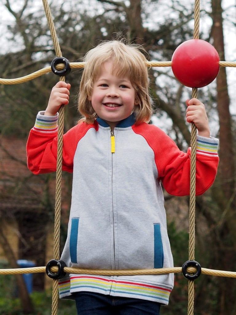 Logan climbing ropes in Frugi jacket - grey body with orange sleeves