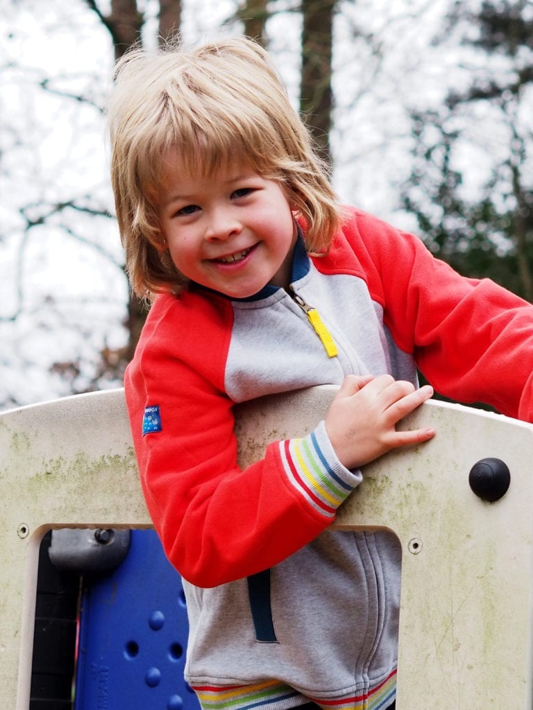 Logan at the top of the climbing frame wearing Frug jacket