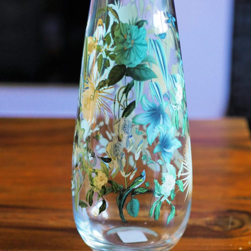 Clear vase with green leaves painted on it