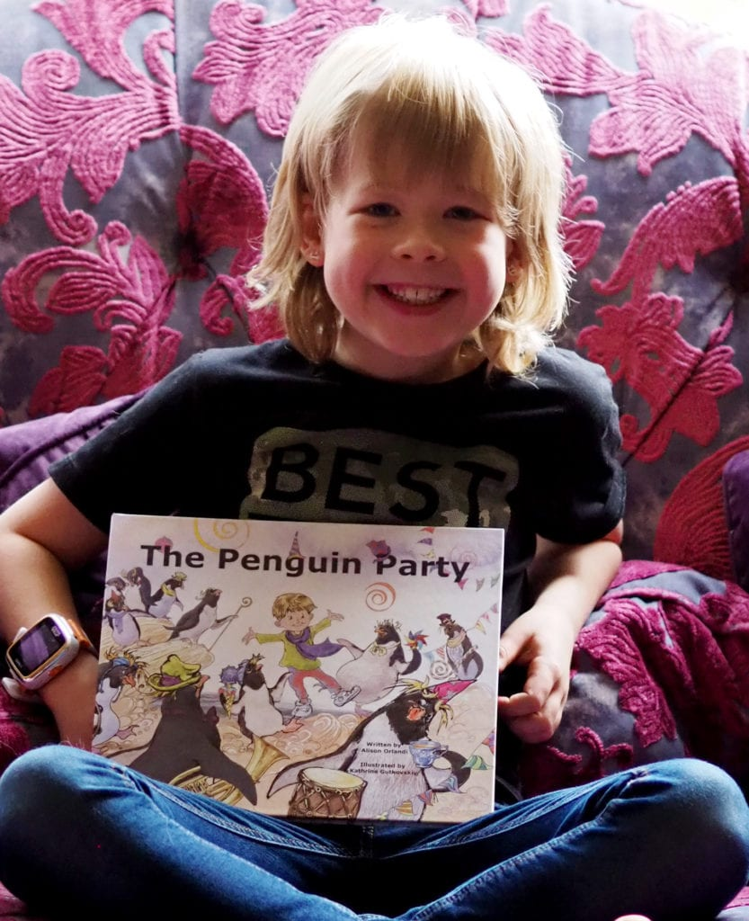 The penguin party book review - Logan sitting on the sofa smiling with the book