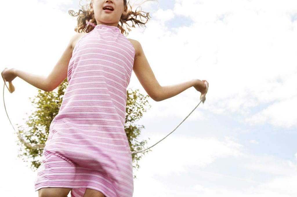 How to Keep Active When Isolating at Home - Young girl skipping in the park with a rope.