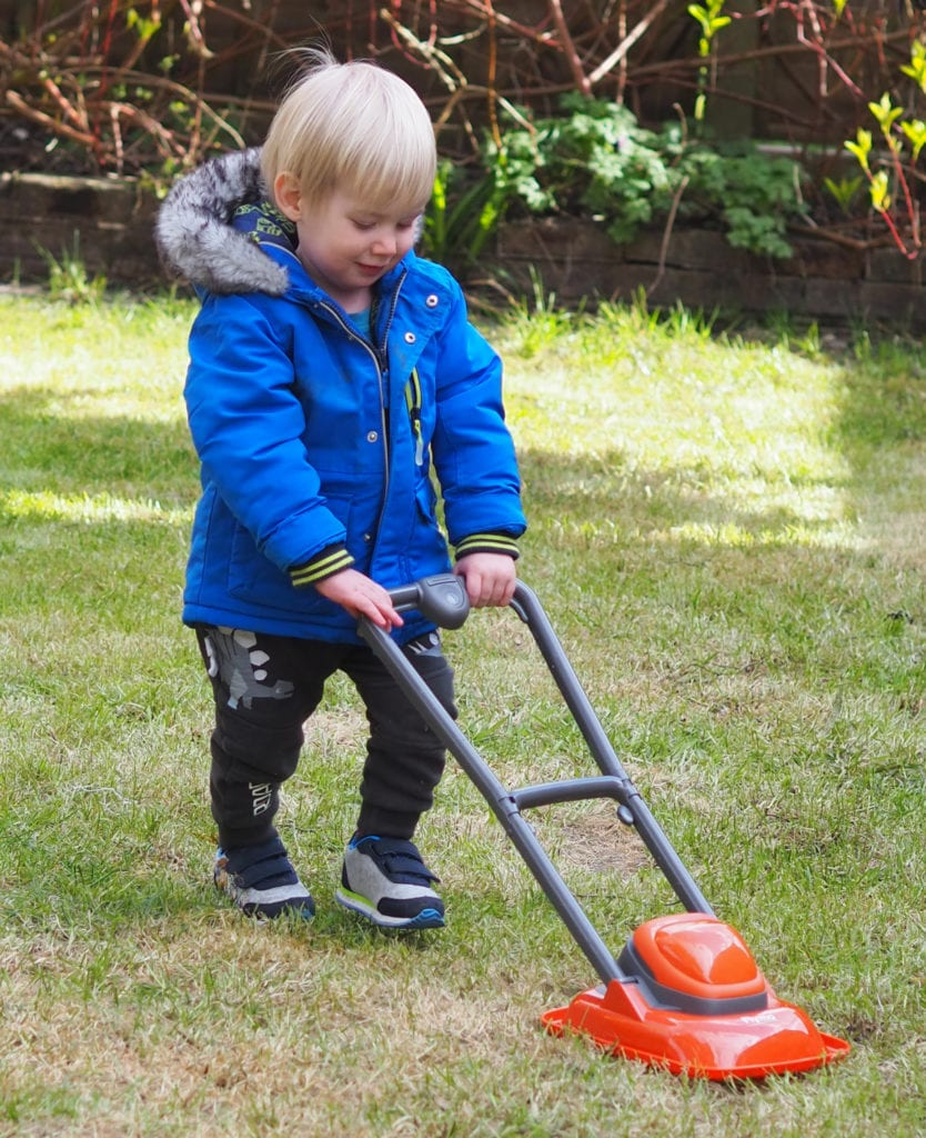 Bo playing with the Casdon lawnmover