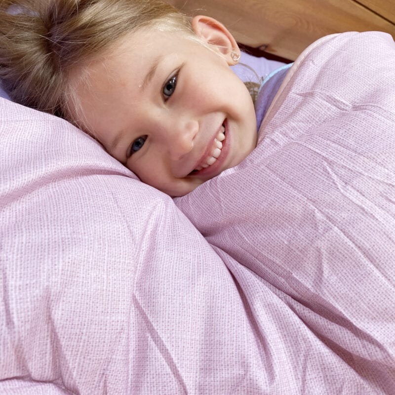 Trendsetter Home Furnishings Review - Aria curled up in bed smiling with a pink duvet