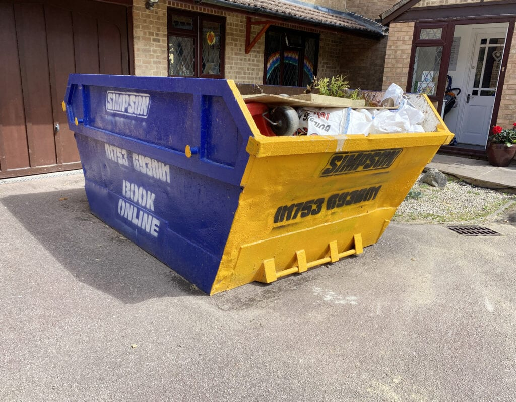 Any Junk Skip Review - pictures of a blue and yellow skip sitting on a drive