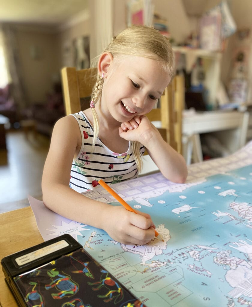 Aria sat at the dining table smiling and colouring large map