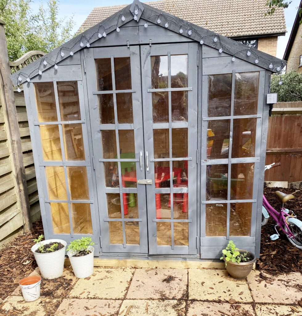 Billy Oh 6 x 8 Summerhouse Review - picture of a wooden summer house with square windows and doors at the front. Painted slate grey and fairy lights hanging on the front.