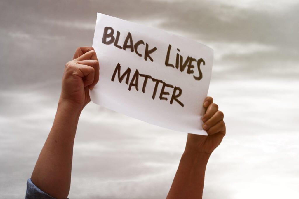 Why Black Lives Matter - hands holding a black lives matter sign in the sky