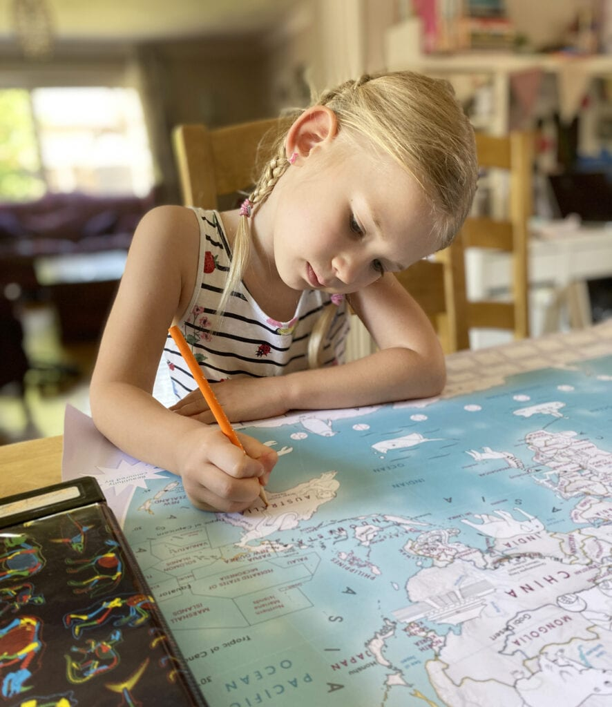 Picture of Aria, hair in two plaits, colouring a large world map