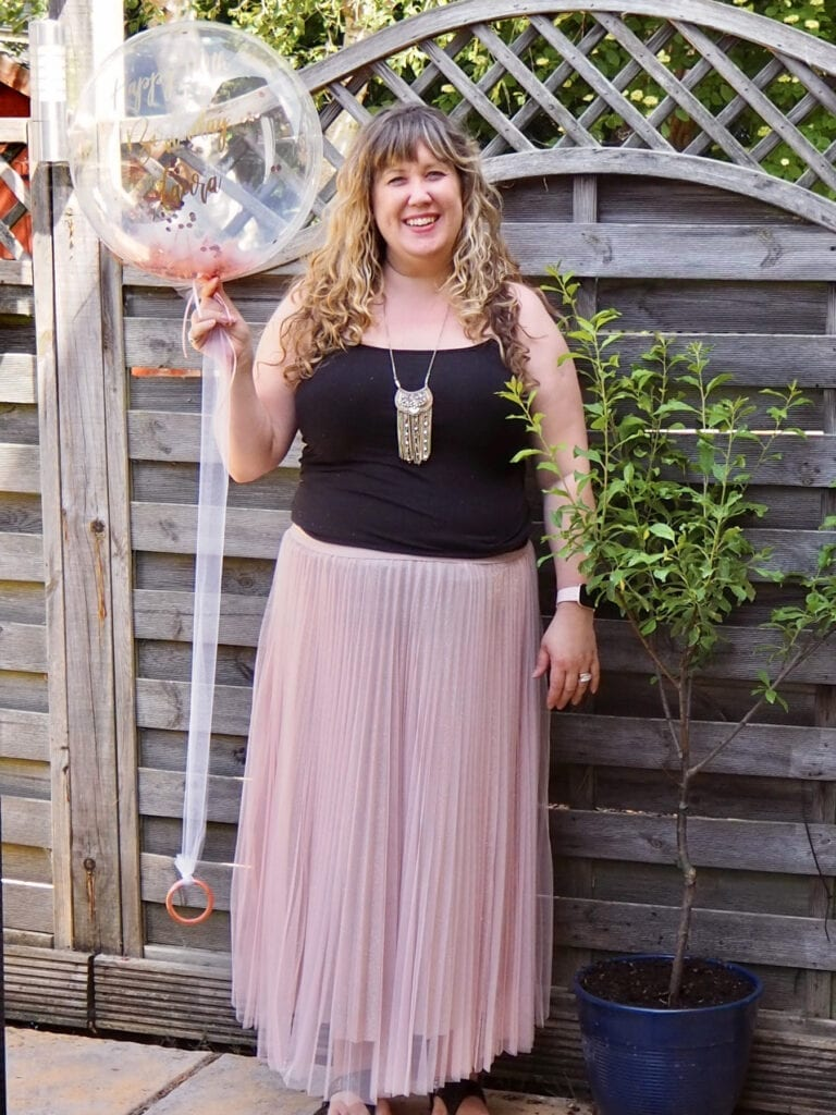 A picture of me in a black top and pink skirt holding a balloon with happy 40th on it in the garden