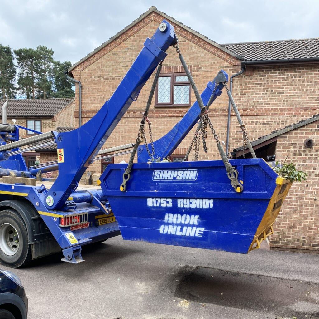 Any Junk Waste Removal Review. Picture of a blue and yellow skip, full of waste being lifted by a large blue lorry.