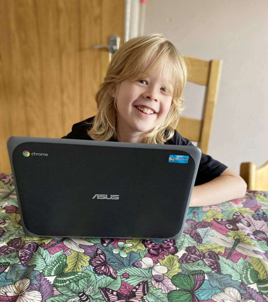 Atom Learning - Filling in the Gaps in your Child's Learning. Picture of a child smiling over the top of a laptop.