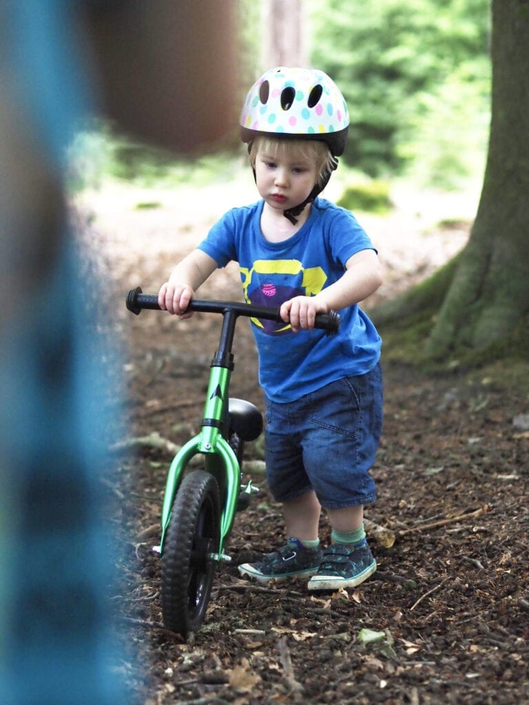 Vitus Nippy Superlight Balance Bike Review. Young boy in the woods, wearing a cycle helmet holding a green balance bike.