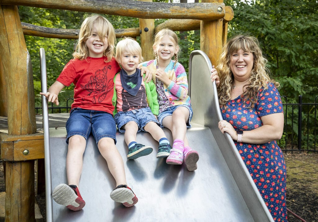 Picture of my three children sat on the top of a slide, with me standing next to it all smiling.