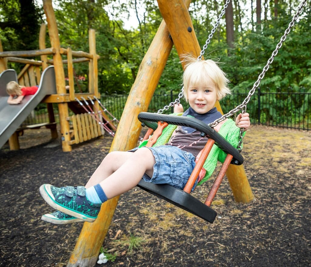 Picture of a toddler on a swing in a lime green cardigan