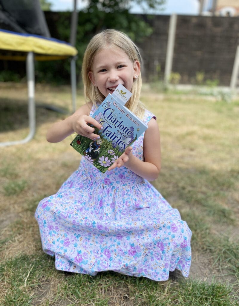CHILDREN'S BOOK REVIEW: Charlotte and the Fairies. Aria sat in the garden in a summer dress holding the book up