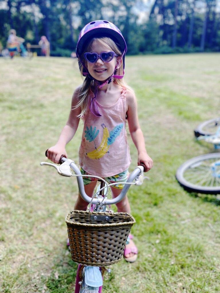 Aria on a bike with a cycle helmet and purple heart sunglasses