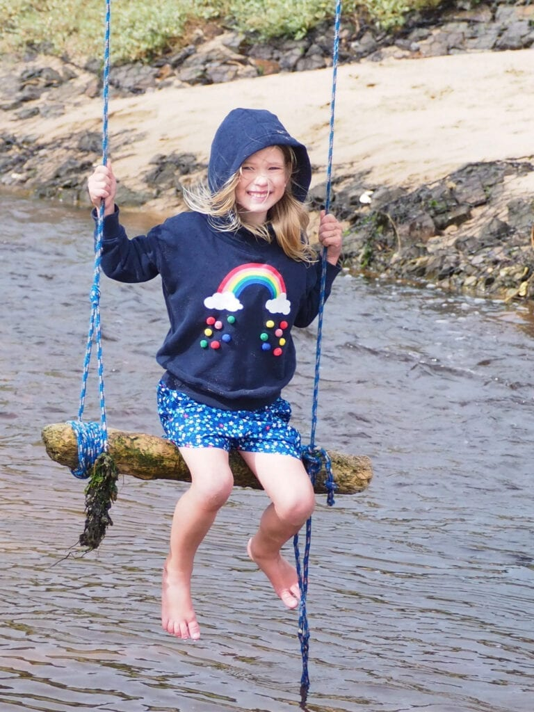 Aria sat on a rope swing over a river wearing a blue hoodie and shorts