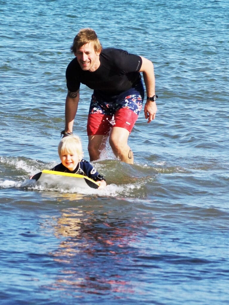 Ben teaching Bo to surf in the sea